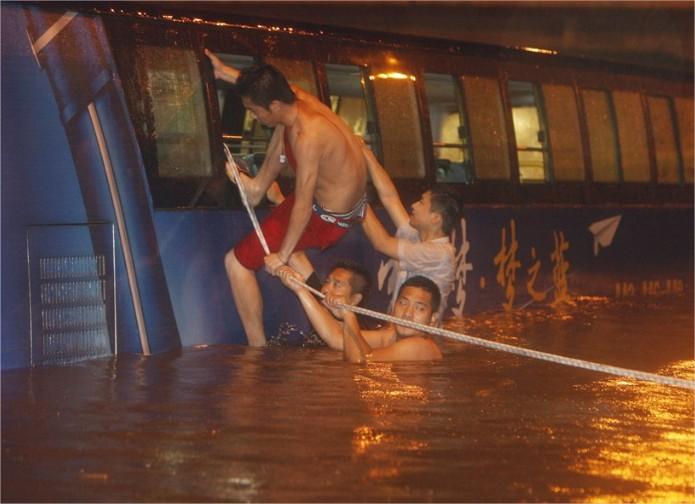 Bomberos y voluntarios rescatan a 11 personas que se habían quedado atrapadas en este autobús de dos pisos.