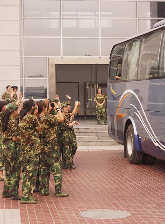 Las nuevas universitarias se despiden del autobús en el que se fueron sus instructores militares.